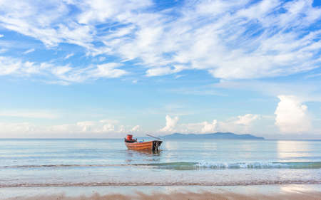 beautiful beach in morning sunrise and cloudy blue sky with fisherman boat