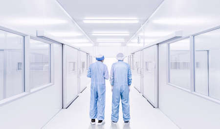 modern interior of laboratory or factory with backside of two science workers in coverall uniform, science development concept background