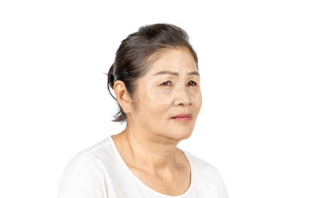 elderly asian woman portrait 60-70 years old no make up with white clothes black hair and hazel eyes isolated on white background Фото со стока