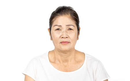 elderly asian woman portrait 60-70 years old no make up with white clothes black hair and hazel eyes isolated on white background Banco de Imagens