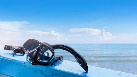 Snorkel mask put on the side of traveling boat ready to use for snorkeling with swimsuit, Vacation and relaxation concept