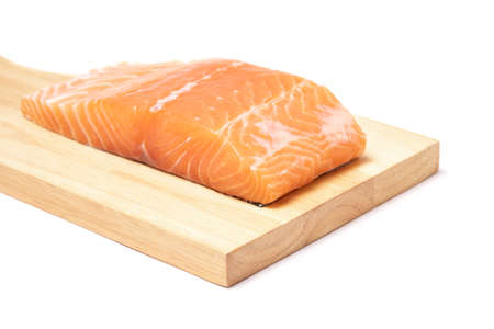 Salmon fish meat slice and put on the wooden chopping block isolated on white background