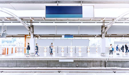 train station platform with blured people and blank billboard for advertising design mock-up