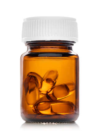 Cápsulas de gel blando de aceite de pescado en botella de vidrio transparente marrón aislado sobre fondo blanco con concepto médico y de salud