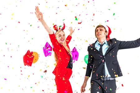 Pareja joven disfruta de la danza con confeti de colores en la fiesta de celebración de año nuevo y aislado sobre fondo blanco.
