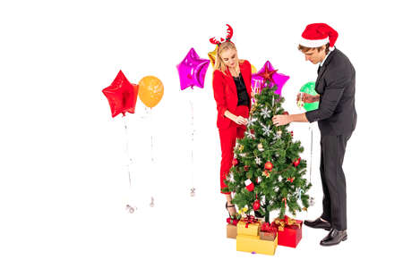 young lovely couple enjoy decorated the christmas tree with ornaments for new year celebration party and isolated on white background