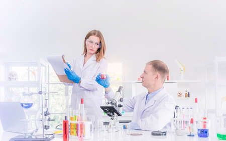 Two scientists working and discus in chemical laboratory, teamwork analysis and scientist working concept