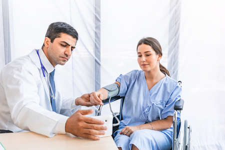 Asian doctor check-up pretty patient atrial pressure by pulse meter at hospital or medical clinic, Health care and Medical concept
