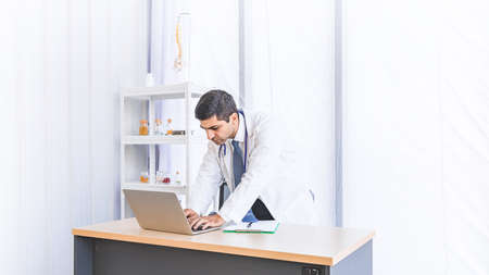 Asian doctor in gown uniform working in seriously at hospital or medical clinic, Healthty and Occupation concept Stock Photo