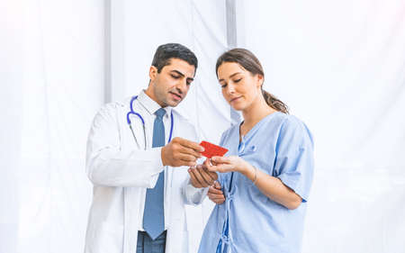 Asian doctor give advice and examination about medicine instruction for pretty patient at hospital or medical clinic, Healthy and Medical concept