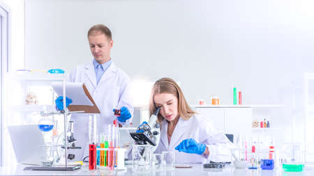 Two scientists researching for some confidential in chemical laboratory, teamwork and scientist working concept