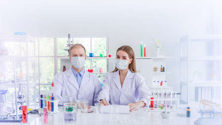 Scientists with masking researching for some confidential in chemical laboratory, teamwork and scientist working concept Stock Photo
