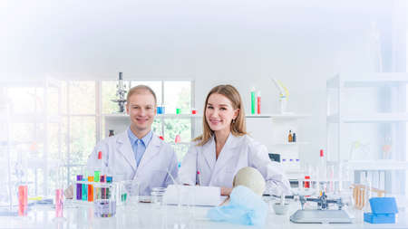Scientists with smiling researching for some confidential in chemical laboratory, teamwork and scientist working concept
