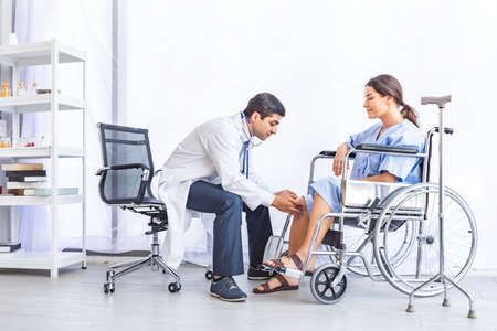 Asian doctor give advice and examination about knee joint for pretty patient at hospital or medical clinic, Healthy and Medical concept Stockfoto