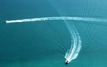 Boat trails crossing blue water photo