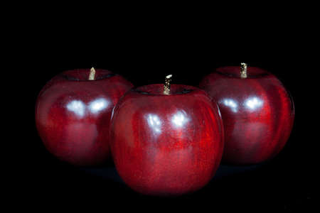 Wooden red apples on black background