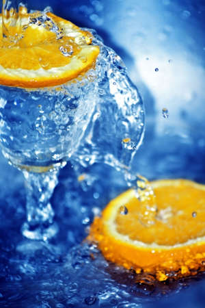 Two slices of orange and a glass in blue clean water photo