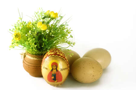 Easter eggs and clay vase with flowers, on white background photo