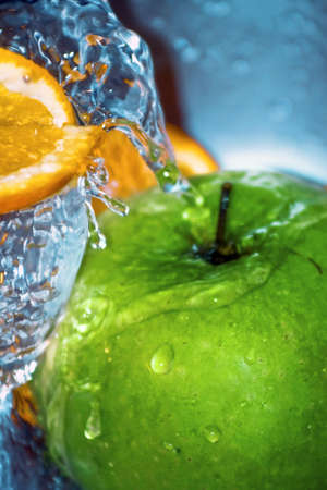 Close-up on water falling above oranges and an apple photo
