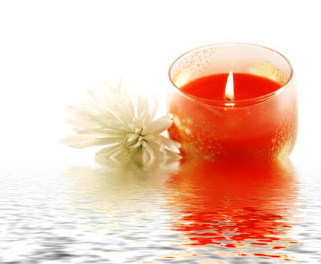 Candle and a white flower reflecting in water photo