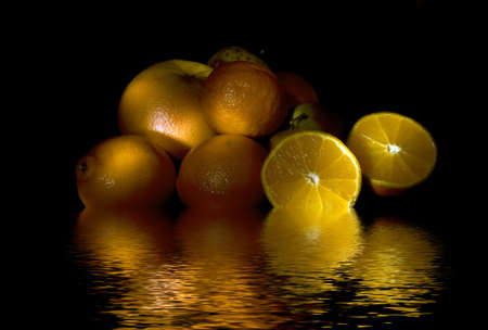 Oranges, lemons, grapefruit and apples reflecting in water photo