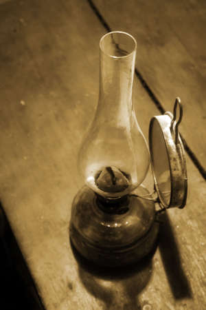 An old lamp standing on a wooden table (vintage)