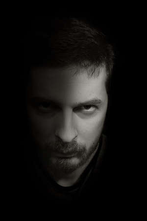 merciless: Low-key portrait of an ominous man emerging from the dark