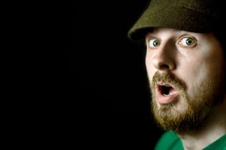 Portrait of a surprised man on black background photo