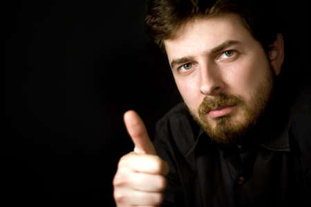 Confident man showing thumb up, on black background Stock Photo - 2924720