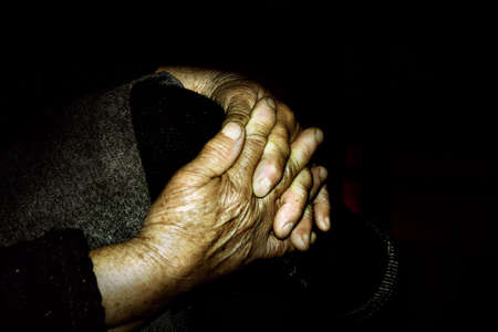 Clopse up on wrinkled hands of an old woman