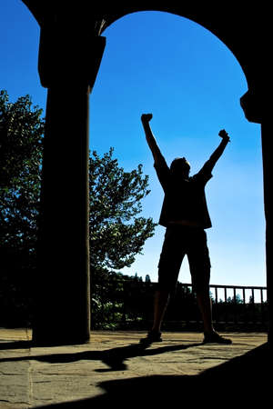 Success concept - man silhouette with hands up expressing victory photo