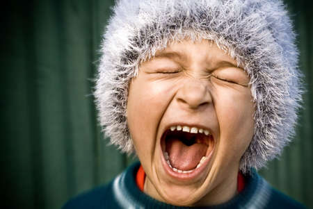 Close-up of portrait of crazy kid screaming loudly photo