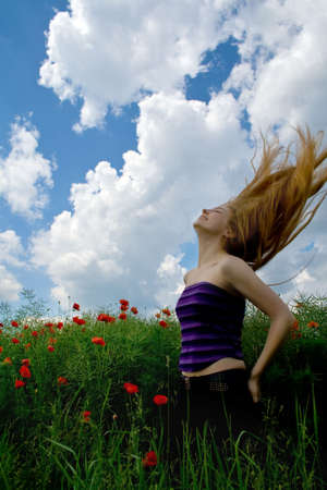 Girl with beautiful blond hair in splendid green meadow photo