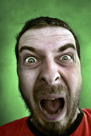 Portrait of shouting shocked man with big and fearful eyes photo