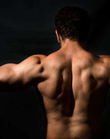 Low key image of muscular male back photo