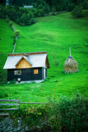 Peaceful view of green hill and wooden cottage Stock Photo - 3725943