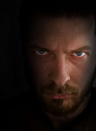 fierce: Low-key portrait - sad and angry looking man Stock Photo