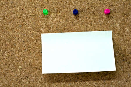 Blank reminder on wooden board and three colorful pins photo