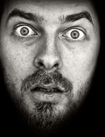 funny bearded man: Face of very amazed man, on black background Stock Photo