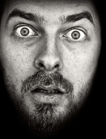 horrified: Face of very amazed man, on black background Stock Photo