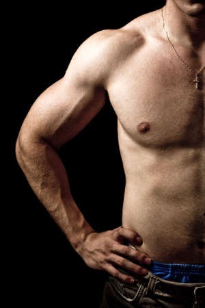 Close-up on muscular man isolated on black background photo