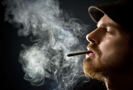 man smoking: Fine art portrait of masculine guy smoking a cigar