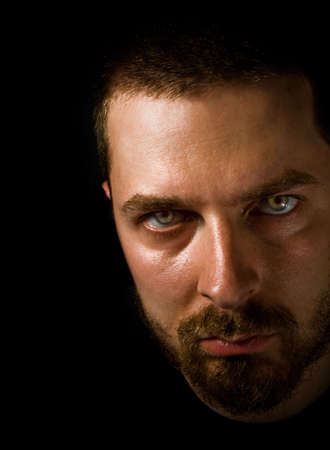 Low-key portrait of sinister man with scary eyes photo