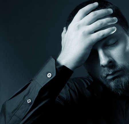Low key portrait of depressed businessman photo
