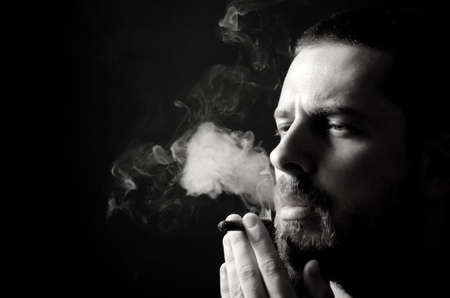 cigar smoking man: Black and white portrait of pensive male smoker