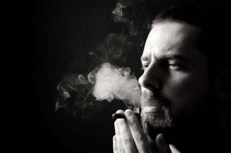hombre fumando puro: En blanco y negro retrato de los pensativo var�n fumador Foto de archivo