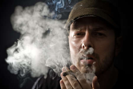 Portrait of cool looking guy smoking a cigar photo