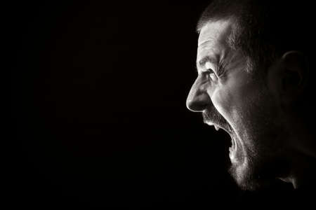 yell: Portrait of screaming angry man on black background Stock Photo