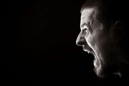 Retrato de hombre gritando enojado sobre fondo negro