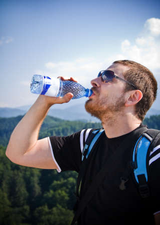 man drinking water: Handsome man drinking water on top of mountain
